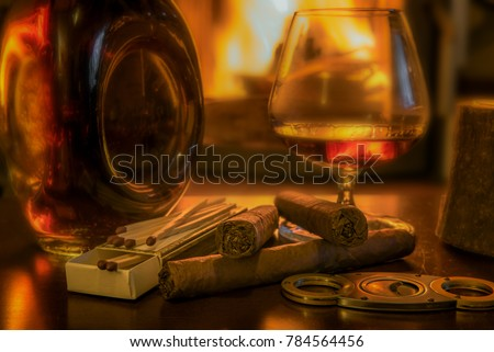 Time to enjoy! Quality cigars and cognac on a wooden table and other accessories such as cigar cutters and matches. In the background a fireplace. Focus on the cigars. Concept: life style or health
