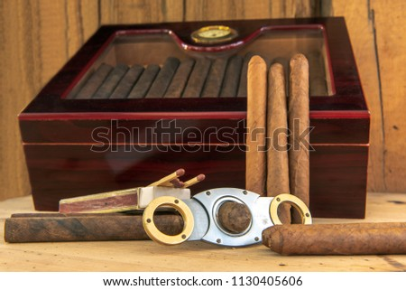 Time to enjoy! Quality cigars and other accessories such as cigar cutters, matches and cigar etui on a wooden table. In the background a humidor in front of a wooden wall. Concentrate on the cigars. C