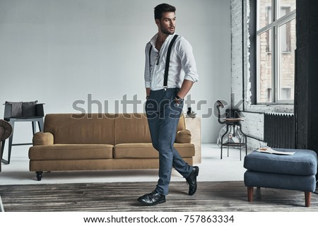 Time to go. Full length of handsome young man in white shirt and suspenders looking away and keeping hands in pockets while walking through the room