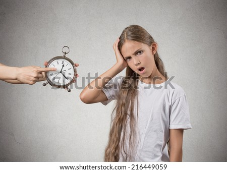 Time to go to bed. Portrait of mom showing kid clock that it is late. She doesn\'t like that, isolated grey wall background. Face expressions, emotions. Difficult parenting concept