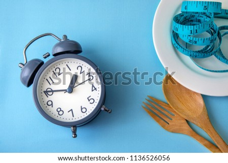 Time to lose weight , eating control or time to diet concept , alarm clock with healthy tool concept decoration on blue background #1136526056