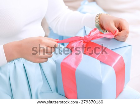 Time to open presents. Close up hands of a girl pulling a red ribbon to open her birthday gift in a blue box