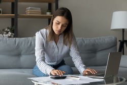 Time to pay bills. Concentrated woman pay domestic utilities at online app calculate fee work with financial papers. Young lady owner renter tenant of house flat engaged in housekeeping at home office