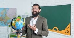 Time to prepare. prepare for exam. college lecturer on geography lesson. back to school. informal education. happy mature teacher holding globe. bearded man geographer work in classroom with map