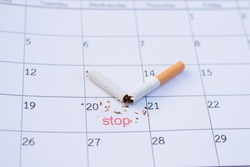 Time to quit smoking. Cigarette butts on the calendar. Concept of choosing a day to quit smoking