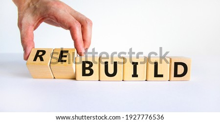 Time to rebuild symbol. Businessman turns wooden cubes and changes the word 'build' to 'rebuild'. Beautiful white background. Business, build or rebuild concept. Copy space. Stockfoto ©
