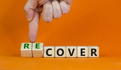 Time to recover symbol. Businessman turns wooden cubes and changes the word 'cover' to 'recover'. Beautiful orange background. Business, cover or recover concept. Copy space.