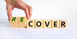 Time to recover symbol. Businessman turns wooden cubes and changes the word 'cover' to 'recover'. Beautiful white background. Business, cover or recover concept. Copy space.