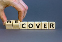 Time to recover symbol. Businessman turns wooden cubes and changes the word 'cover' to 'recover'. Beautiful grey background. Business, cover or recover concept. Copy space.