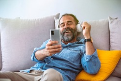 Time to relax. Joyful middle-aged bearded man in wireless headphones listening to music, copy space, closeup. Happy handsome man in headset with eyes closed relaxing on couch in living room