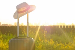 Time to Relax, traveling suitcase with hat standing on the floor out the room, travel lifestyle concept. The journey and  vacation concept or business travel, Finding solitude in the wilderness.