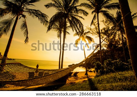 Time to relax with silhouette of hammock and coconut tree at the beach on sunset time in Samui Island Thailand