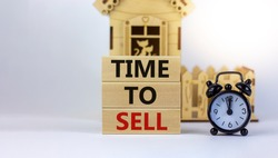 Time to sell real estate. Wooden blocks form the words 'time to sell' near miniature house. Black alarm clock. Beautiful white background. Business concept. Copy space.
