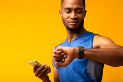 Time To Start. Portrait of black muscular man looking at smartwatch, holding smartphone, checking fitness tracker