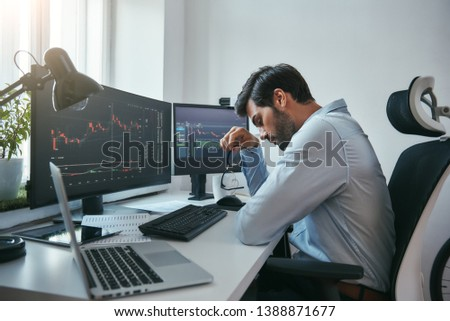 Time to take a break. Side view of tired young businessman or trader holding eyeglasses and feeling tired while working with data and charts on computers at his modern office.