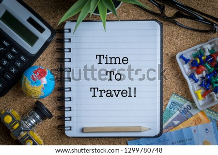 TIME TO TRAVEL inscription written on book with globe,eyeglasses, calculator, camera, pencil and vase on wooden background with selective focus and crop fragment. Business and education concept Stock fotó ©