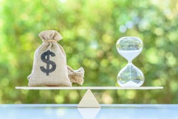 Time value of money, asset growth over time, financial concept : Dollar bags, sand clock or hourglass on a balance scale in equal position, depicts investment in long-term equity for more money growth