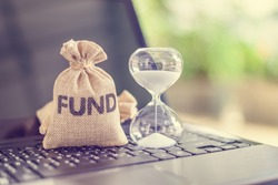 Time value of money, long term equity fund investment for sustainable growth, financial concept : Bag of fund, hourglass on a laptop, depicts online portfolio asset allocation for best expected return