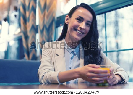 Time with pleasure. Beautiful brunette keeping smile on her face while drinking fresh juice #1200429499