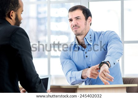 Time work. Serious businessman sitting at the negotiating table in the office and indicates your watch. Business people dressed in formal wear