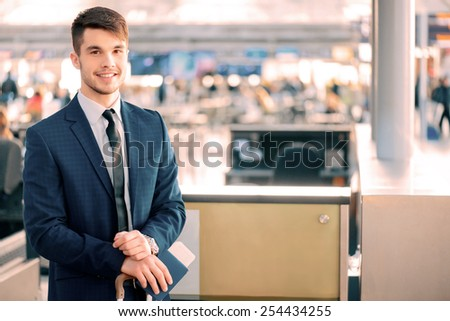 Timely check-in. Handsome young businessman in suit holding his passport with ticket and luggage while standing against airline check in counter in the airport
