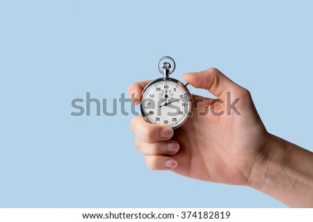timer held in hand, blue background - Shutterstock ID 374182819