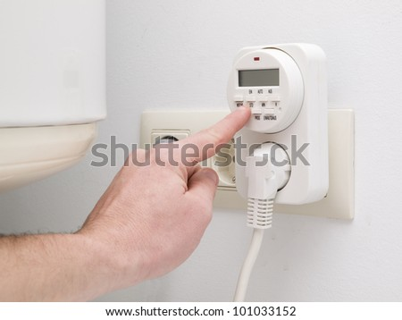 Timer to save energy for domestic purposes. A person is programming.