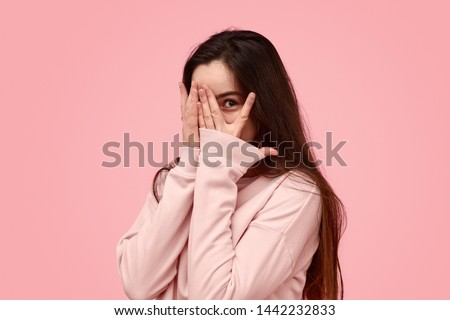 Timid teen girl with long hair covering face with hand and peeking through fingers against pink background