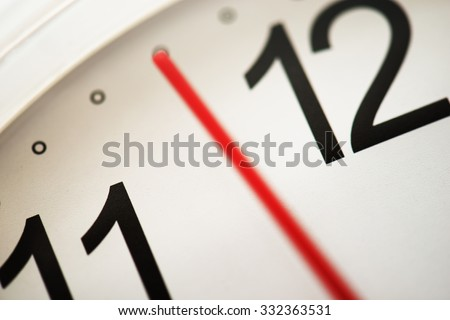 Timing or moment. Waiting for the right timing. Few minutes or seconds to the hour. Focus on clock face letter (needle has blur/ movement).  Extremely shallow depth of focus. Impression shot.