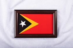 Timor-Leste flag in a realistic frame on white cloth background flat lay photo