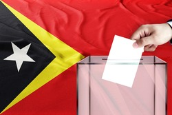timor leste flag, timor leste  the symbol of elections Male hand puts down a white sheet of paper with a mark as a symbol of a ballot paper against the background of the