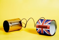 tin can phone with British flag.communication concept on yellow.