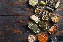Tin cans for fish with different types of seafood, opened and closed cans with Saury, mackerel, sprats, sardines, pilchard, squid, tuna, over dark wood old table flat lay top view space for text