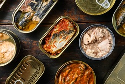 Tin cans for fish with different types of seafood, opened and closed cans with Saury, mackerel, sprats, sardines, pilchard, squid, tuna, over dark wood old table close up top view.