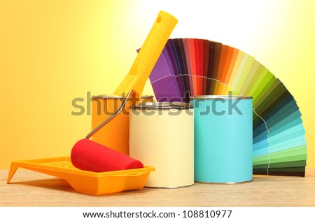 tin cans with paint, roller, brushes and bright palette of colors on wooden table on yellow background