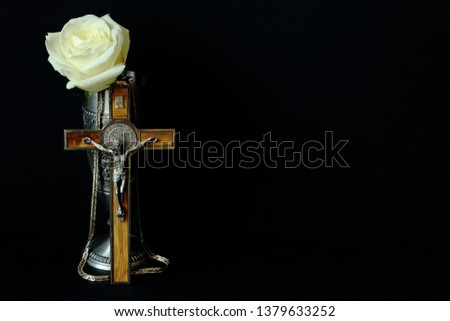Tin cup for wine, crucifix with wooden inlay (souvenirs from Germany) and white rose on black background. Symbolic concept — faith, Christianity, resurrection, life. Minimal style. #1379633252