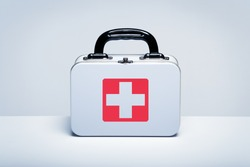 Tin first aid kit with cross emblem on grey background