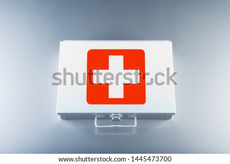 Tin first aid kit with cross emblems on grey background #1445473700