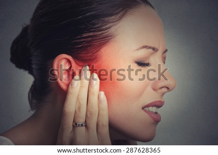 Tinnitus. Closeup up side profile sick female having ear pain touching her painful head isolated on gray wall background