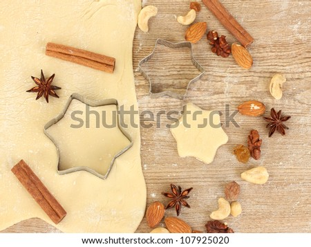 tins of cookies on the rolled out dough with herbs on a wooden table close-up