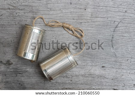 tins telephone with rope connecting on wooden background