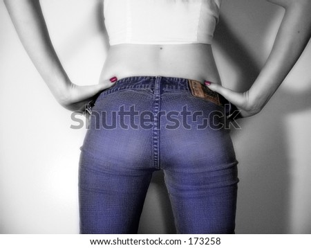 Tinted black and white of female figure in jeans, back view