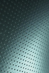 Tinted blue or green metal background. Dark vertical technical wallpaper. Perforated aluminum surface with many holes. Macro