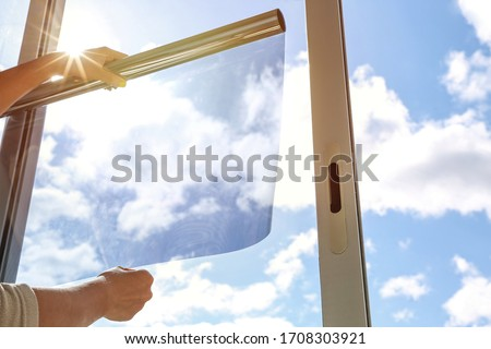 Photo of  tinted glass in the house. window dimming by dark film. hands apply tint film to the window. tint film on sky background. sky view through tinted glass