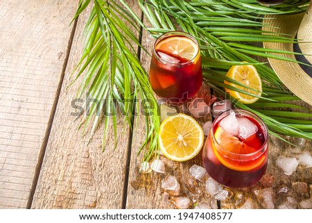 Tinto de Verano or vino de verano, Spanish Wine Cocktail. Refreshment acoholic drink sangria. Cool iced alcohol beverage with lemon juice and slices, wooden background with summer tropical decor  Foto stock ©