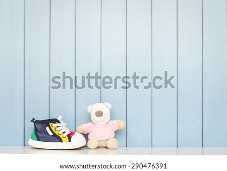 Tiny baby shoes and teddy bear on the table in baby\'s room