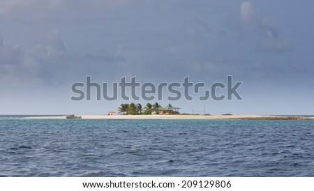 Tiny Caribbean Island with White Sand Beach, Palm Trees and  Umbrellas