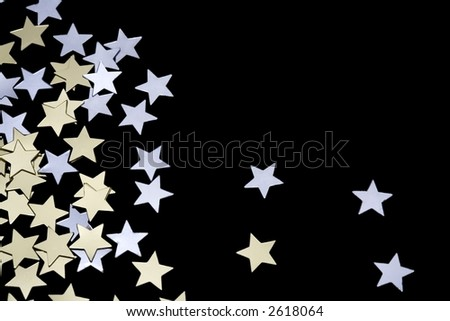 Tiny golden and silver stars isolated on black background. Space for copy.