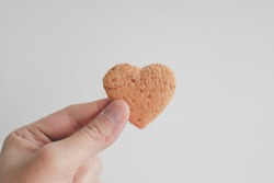Tiny heart shape of bread in hand. Concept of love and care in Valentine day.