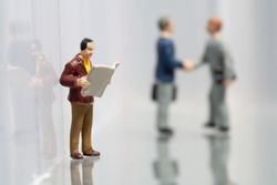 Tiny little miniature model of a man reading the newspaper while taking a break at work with two colleagues shaking hands in the background